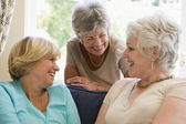 Three women in living room talking and smiling — Stock Photo