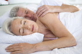 Couple lying in bed together sleeping — Foto de Stock