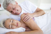 Man waking woman lying in bed sleeping — Stock Photo