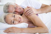 Couple lying in bed together smiling — Stock Photo