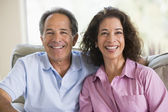 Couple relaxing in living room and laughing — Stock Photo