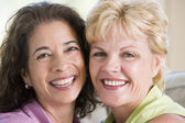 Two women in living room smiling — Stock Photo