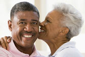 Couple relaxing indoors kissing and smiling — Stock Photo