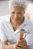 Woman holding hammer looking unsure — Stock Photo