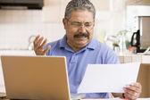 Muž v kuchyni s notebookem a papírování frustrovaný — Stock fotografie