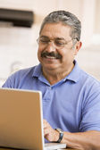 Man in kitchen with laptop smiling — Stock Photo