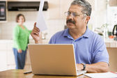 Man in kitchen with laptop and paperwork with woman in backgroun — Stock Photo