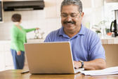 Man in kitchen with laptop smiling with woman in background — Stok fotoğraf
