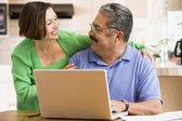 Par i köket med laptop leende — Stockfoto
