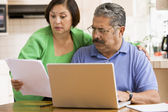 Couple in kitchen with laptop and paperwork — Stock Photo