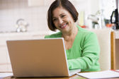 Woman in kitchen with laptop smiling — Stock Photo