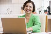 Kadın gülümseyerek laptop ile mutfakta — Stok fotoğraf