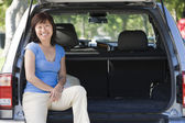 Woman sitting in back of van smiling — Stock Photo