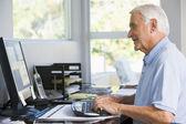 человек в домашнем офисе, с помощью компьютера улыбается — Стоковое фото
