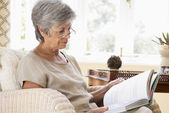 Woman in living room reading book — Stock Photo