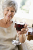 Woman in living room with glass of wine smiling — Stock Photo