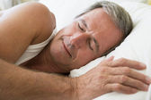 Man lying in bed sleeping — Stock Photo