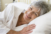 Woman lying in bed smiling — Stock Photo