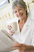 Woman in bedroom with coffee and newspaper smiling — Stock Photo