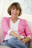 žena v obýváku s úsměvem — Stock fotografie