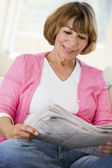Woman in living room reading newspaper smiling — Stock Photo