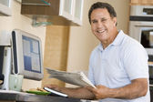 Man in kitchen with computer and newspaper smiling — Stock Photo