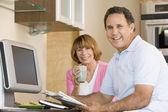 Paar in keuken met koffie en krant glimlachen — Stockfoto