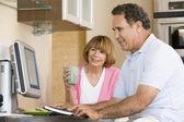 Dvojice v kuchyni s počítačem a kávy s úsměvem — Stock fotografie
