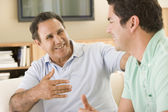 Two men in living room talking and smiling — Stock Photo