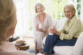 Three women in living room with coffee smiling — Stock Photo