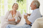 Couple in living room with coffee smiling — Stock Photo