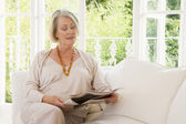 Woman in living room reading newspaper — Stock Photo