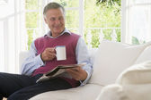 Man in living room with coffee reading newspaper smiling — Stock Photo