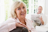Woman in living room smiling with man in background reading news — Stock Photo