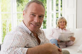 Man in living room smiling with woman in background reading news — Stock Photo