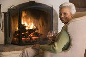 Vrouw in woonkamer met drankje lachende — Stockfoto