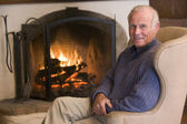 Man sitting in living room by fireplace smiling — Stockfoto