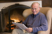 Man sitting in living room by fireplace with newspaper smiling — Stock Photo