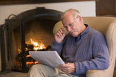 Man sitting in living room by fireplace with newspaper — Stock Photo