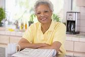 женщина с улыбкой газета — Стоковое фото