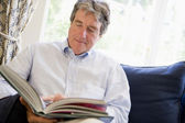 Man relaxing with book in living room — Stockfoto