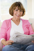 Woman relaxing with newspaper in living room and smiling — Stock Photo