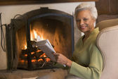 Woman sitting in living room by fireplace with newspaper smiling — Stock Photo