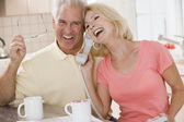 Couple in kitchen using telephone together and laughing — Stock Photo