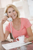 Woman in kitchen using telephone and smiling — Stock Photo