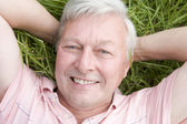 Man lying in grass smiling — Stock Photo