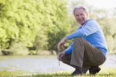 Man outdoors at park by lake smiling — Stock Photo