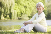 Woman outdoors at park by lake smiling — Stockfoto