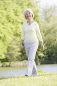 Woman walking outdoors at park by lake smiling — Stock Photo