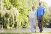 Couple walking outdoors at park by lake smiling — Stock Photo